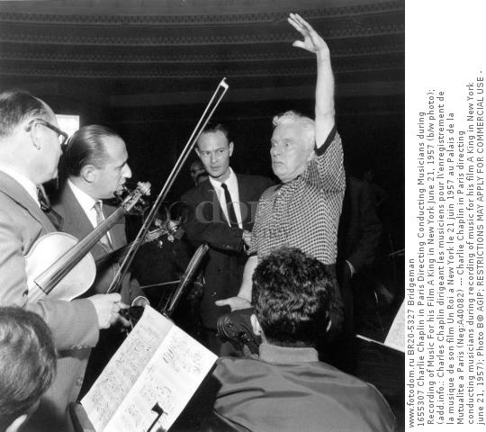 1655307 Charlie Chaplin in Paris Directing Conducting Musicians during Recording of Music For his Film A King in New York June 21, 1957 (b/w photo); (add.info.: Charles Chaplin dirigeant les musiciens pour l\'enregistrement de la musique de son film Un Roi a New York le 21 juin 1957 au Palais de la Mutualite a Paris (Neg:A40082) --- Charlie Chaplin in Paris directing conducting musicians during recording of music for his film A King in New York june 21, 1957); Photo В© AGIP; RESTRICTIONS MAY APPLY FOR COMMERCIAL USE - PLEASE CONTACT US;  out of copyright.