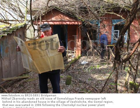 Mikhail Zbarovsky reads an old issue of Gomelskaya Pravda newspaper left behind in his abandoned house in the village of Vezhishche, the Gomel region, that was evacuated in 1986 following the Chernobyl nuclear power plant disaster, 2012 (photo)