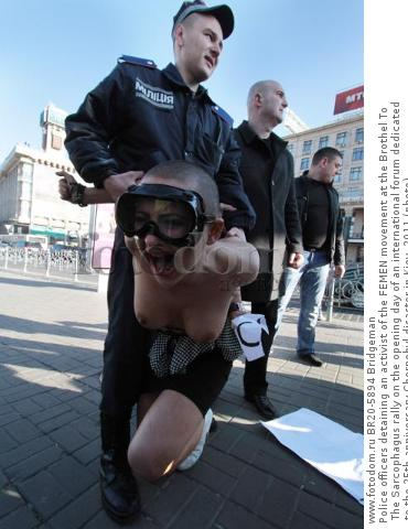Police officers detaining an activist of the FEMEN movement at the Brothel To The Sarcophagus rally on the opening day of an international forum dedicated to the 25th anniversary Chernobyl disaster in Kiev, 2011 (photo)