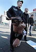 Police officers detaining an activist of the FEMEN