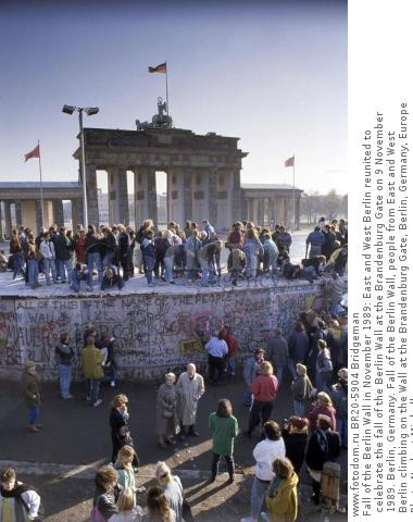 Fall of the Berlin Wall in November 1989: East and West Berlin reunited to celebrate the fall of the Berlin Wall at the Brandenburg Gate on 9 November 1989. Berlin, Germany. Fall of the Berlin Wall, people from East and West Berlin climbing on the Wall at the Brandenburg Gate, Berlin, Germany, Europe Photo Norbert Michalke
