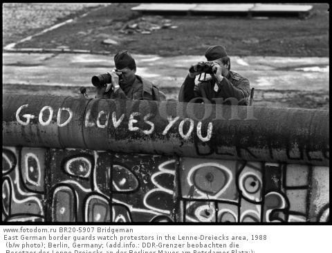 East German border guards watch protestors in the Lenne-Dreiecks area, 1988 (b/w photo); Berlin, Germany; (add.info.: DDR-Grenzer beobachten die Besetzer des Lenne-Dreiecks an der Berliner Mauer am Potsdamer Platz;); .