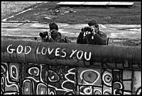 East German border guards watch protestors in the