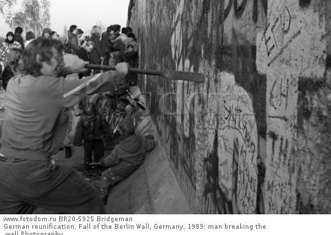 German reunification, Fall of the Berlin Wall, Germany, 1989: man breaking the wall Photography