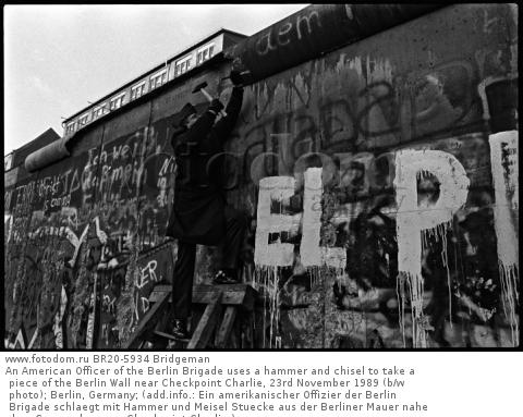 An American Officer of the Berlin Brigade uses a hammer and chisel to take a piece of the Berlin Wall near Checkpoint Charlie, 23rd November 1989 (b/w photo); Berlin, Germany; (add.info.: Ein amerikanischer Offizier der Berlin Brigade schlaegt mit Hammer und Meisel Stuecke aus der Berliner Mauer nahe dem Grenzuebergang Checkpoint Charlie;); .