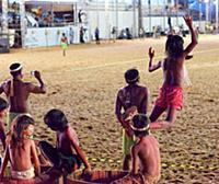 Indigenous children play on the sidelines during t