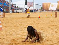 Indigenous girl plays in the sand as the spear thr