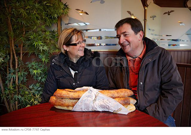French couple chatting in a cafe with baguettes on their table. Le Perreux-sur-Marne  Val-de-Marne  France.