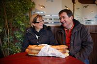 French couple chatting in a cafe with baguettes on