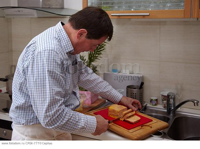 Man slicing foie gras in his kitchen. Paris  France.