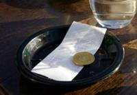Receipt (in English) and 50 cent coin on table of