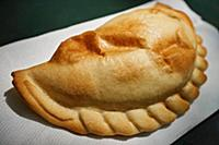 A baked Argentine style empanada sold by a Mahatta