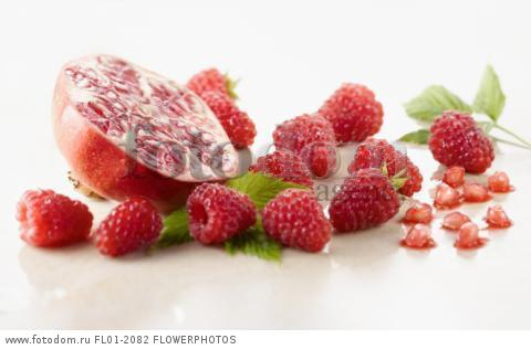Raspberry, Rubus idaeus cultivar and Pomegranate, Punica cultivar cut in half surrounded with several raspberries and leaves on white marble. Selective focus.
