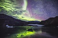 Aurora borealis over glacier and coastal mountains