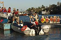 Tourists on municipal dock boarding zodiac boats,