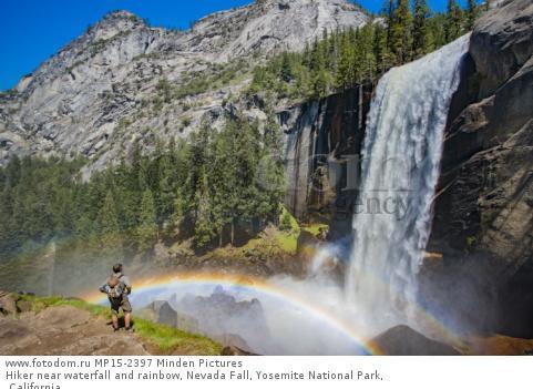 Hiker near waterfall and rainbow, Nevada Fall, Yosemite National Park, California