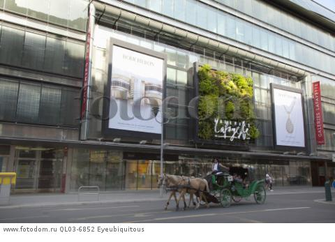 Germany, Berlin, Mitte, Vertical planting on the exterior of Galleries Lafayette on Friedrichstrasse with horse and carriage passing.