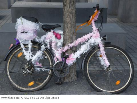 Germany, Berlin, Mitte, Holocaust Memorial with a bicycle decorated with pink and white ribbons leaning against a tree.