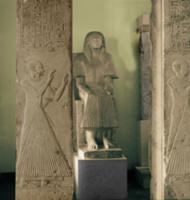 Limestone statue and two pillars with reliefs of a