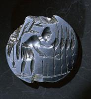 Intaglio amulet showing a reaper stooping to cut c