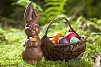 A chocolate bunny and a basket of Easter eggs in a