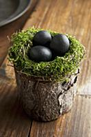 Easter eggs in moss nest on wooden surface