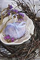 Light blue Easter egg with bow in nest