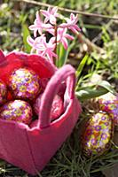 Chocolate Easter eggs in a pink felt basket in a m