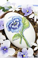 Goose egg decorated with pansy using napkin decoup