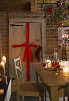 A wooden door decorated with a bow and a stocking