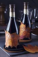 Small wine bottles decorated with painted autumn l
