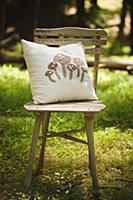 Mushroom-patterned cushion on chair in sunny woodl