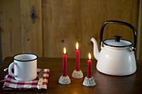 Three lit red candles in cake-shaped candle holder