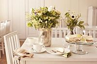 Table set with coffee, cake and vases of flowers