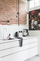 Whit fitted kitchen with exposed brick wall