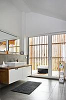 Modern bathroom with high ceiling and glass wall l