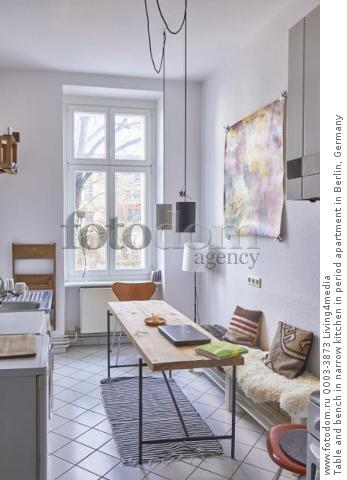 Table and bench in narrow kitchen in period apartment in Berlin, Germany