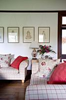 Red and floral cushions on checked sofas in living