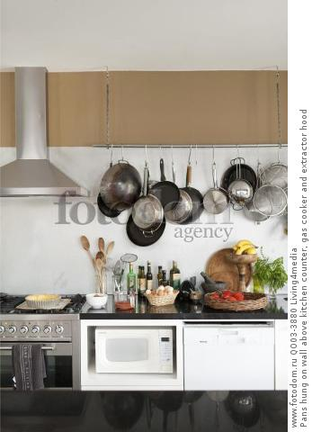 Pans hung on wall above kitchen counter, gas cooker and extractor hood