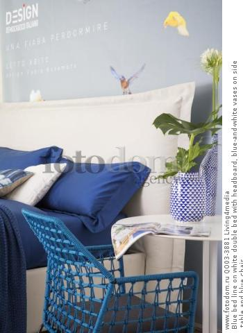 Blue bed line on white double bed with headboard, blue-and-white vases on side table and blue chair