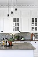Pendant lamps above island counter in white countr
