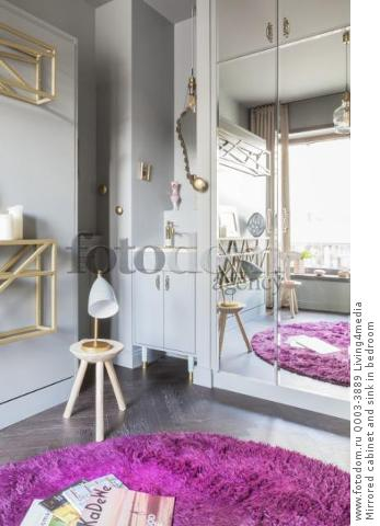 Mirrored cabinet and sink in bedroom