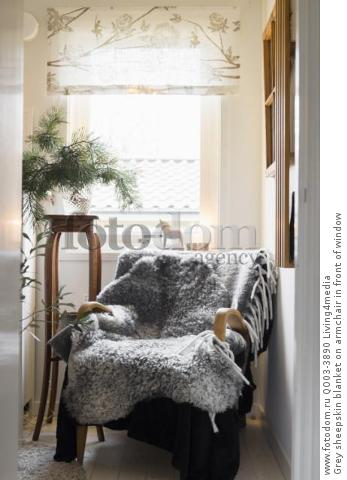 Grey sheepskin blanket on armchair in front of window