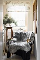 Grey sheepskin blanket on armchair in front of win