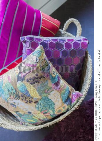 Cushions with patterns of birds, hexagons and stripes in basket