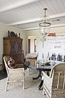 Wicker chairs at round table in dining room with w