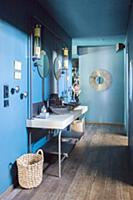 Washstand with twin sinks against blue wall in hal