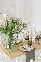 Table set for wedding with vase of tulips, dry twi