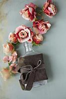 Fabric roses and bottle tied with leather bow on g