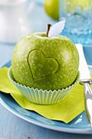 Green apple carved with love heart in cake case on